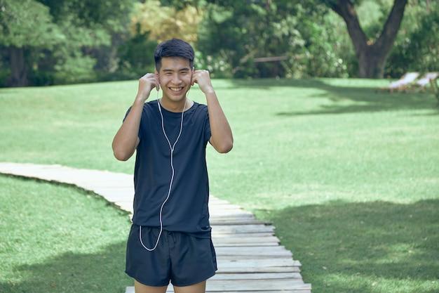 Junge hübsche asiatische ausübung im park, die einen fitness-tracker trägt
