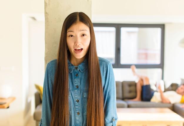 Junge hübsche asiatische frau, die ein t-shirt drinnen trägt