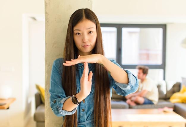 Junge hübsche asiatische frau, die ernst, streng, wütend und unzufrieden aussieht und auszeitzeichen macht