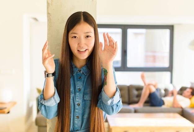 Junge hübsche asiatische frau, die in panik oder wut schreit, schockiert, verängstigt oder wütend, mit händen neben kopf