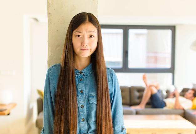 Junge hübsche asiatische frau, die sich verwirrt und zweifelhaft fühlt, sich wundert oder versucht, zu wählen oder eine entscheidung zu treffen