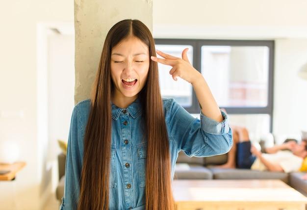 Junge hübsche asiatische frau, die unglücklich und gestresst aussieht, selbstmordgeste, die waffenzeichen mit hand macht, zeigt auf kopf