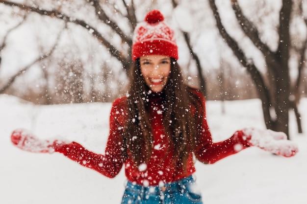 Junge hübsche aufrichtige lächelnde glückliche frau in den roten handschuhen und im hut, die den gestrickten pullover tragen, der im park im schnee spielt, warme kleidung, spaß haben