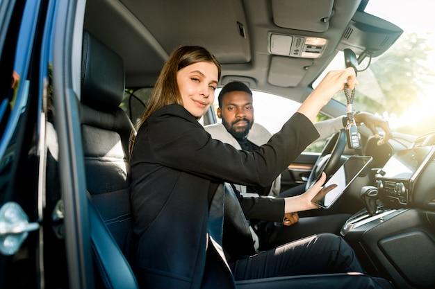 Junge hübsche autohändlerin der kaukasischen frau, die autoschlüssel und digitales tablett hält, während sie im auto mit ihrem lächelnden hübschen kunden, afrikanischen geschäftsmann sitzt