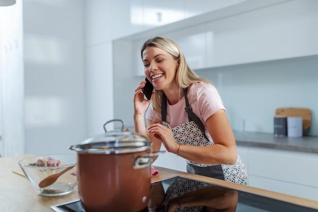Junge hübsche blonde faule hausfrau, die in der küche steht und am telefon spricht, während topf mit mittagessen auf dem herd ist.