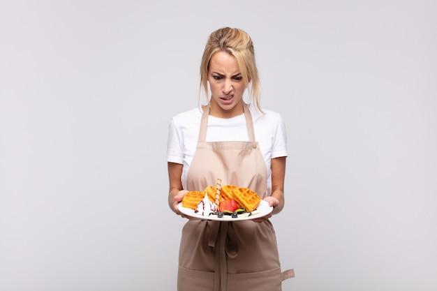 Junge hübsche blonde frau bäcker. waffel-konzept
