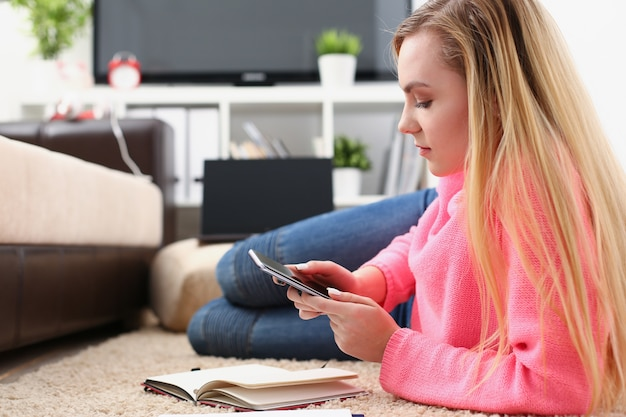 Junge hübsche blonde frau, die auf sofa sitzt und smartphone in händen hält