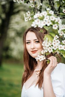 Junge hübsche blonde frau, die blumen im blühenden kirschblüte-garten riecht.