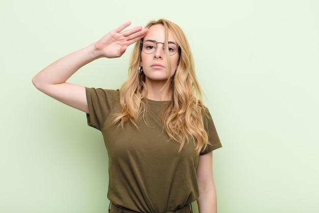 Junge hübsche blonde frau, die die kamera mit einem militärischen gruß in einem akt der ehre und des patriotismus begrüßt und respekt gegen flache farbwand zeigt