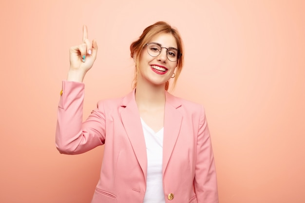 Junge hübsche blonde frau, die fröhlich und glücklich lächelt und mit einer hand nach oben zeigt, um raum zu kopieren. geschäftskonzept