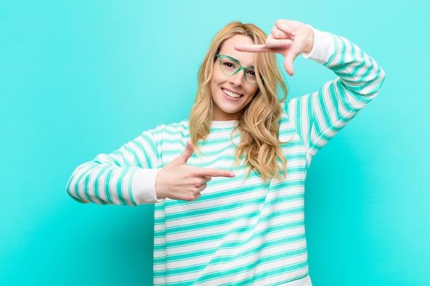 Junge hübsche blonde frau, die glücklich, freundlich und positiv fühlt, lächelt und ein porträt oder fotorahmen mit händen gegen flache farbwand macht