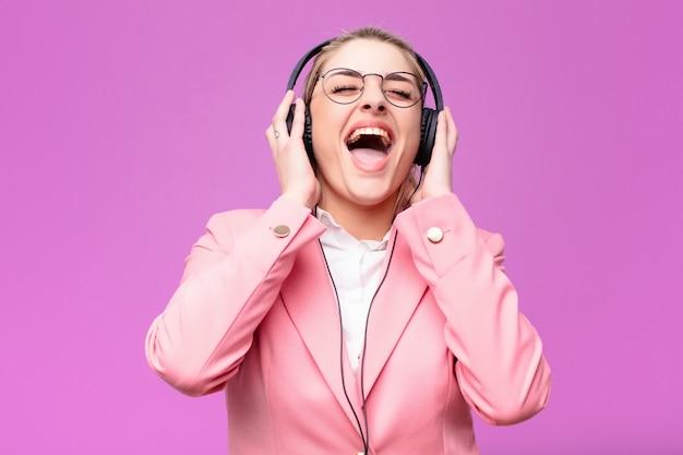 Junge hübsche blonde frau, die musik mit kopfhörern hört