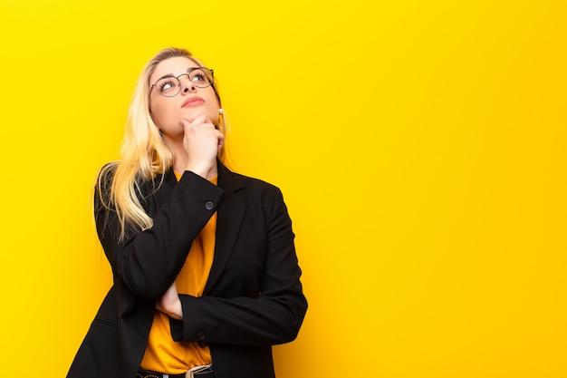 Junge hübsche blonde frau, die nachdenklich fühlt, sich wundert oder ideen vorstellt, tagträumen und nach oben schaut, um raum über gelber wand zu kopieren