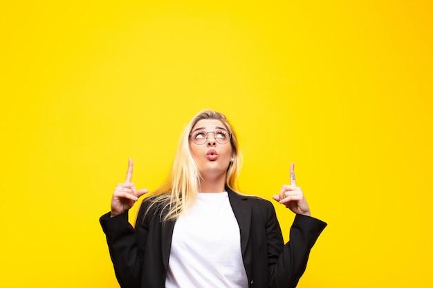 Junge hübsche blonde frau, die schockiert, erstaunt und mit offenem mund aussieht und mit beiden händen nach oben zeigt, um platz gegen gelbe wand zu kopieren