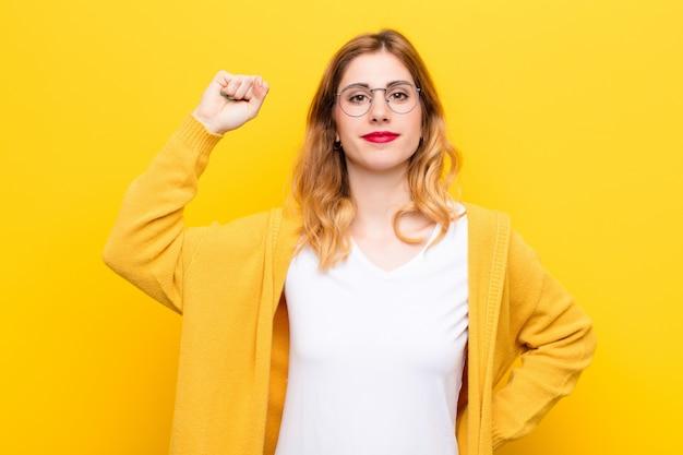 Junge hübsche blonde frau, die sich ernst, stark und rebellisch fühlt, die faust erhebt, protestiert oder für die revolution gegen die gelbe wand kämpft