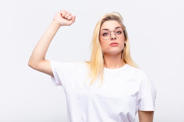 Junge hübsche blonde frau, die sich ernst, stark und rebellisch fühlt, die faust erhebt, protestiert oder für die revolution gegen die weiße wand kämpft