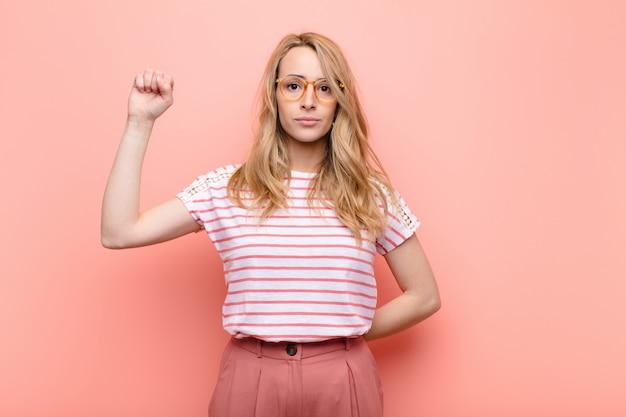Junge hübsche blonde frau, die sich ernst, stark und rebellisch fühlt, faust erhebt, protestiert oder für die revolution gegen flache farbwand kämpft