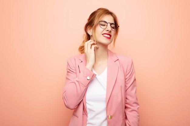 Junge hübsche blonde frau, die sich gestresst, frustriert und müde fühlt und schmerzhaften nacken reibt, mit einem besorgten, besorgten blick. geschäftskonzept