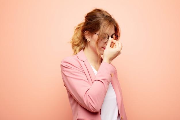 Junge hübsche blonde frau, die sich gestresst, unglücklich und frustriert fühlt, die stirn berührt und unter migräne mit starken kopfschmerzen leidet