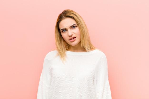 Junge hübsche blonde frau, die sich verwirrt und verwirrt fühlt, mit einem dummen, fassungslosen ausdruck, der etwas unerwartetes gegen rosa flache wand betrachtet