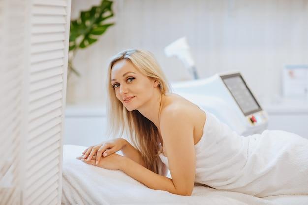 Junge hübsche blonde frau im weißen bademantel, der auf dem kosmetikstuhl gegen haarentfernungsmaschine und grüne pflanze legt. speicherplatz kopieren.