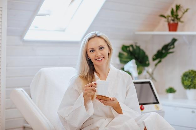 Junge hübsche blonde frau im weißen bademantel, der mit tasse kaffee in einem haarentfernungsschrank aufwirft.