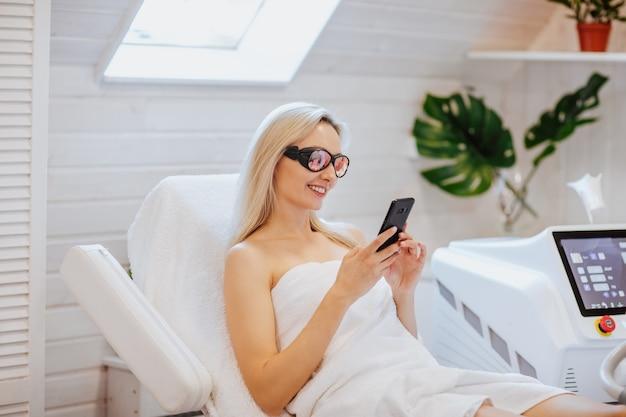 Junge hübsche blonde frau im weißen handtuch und in der schwarzen brille, die das telefon in einem haarentfernungsschrank halten.