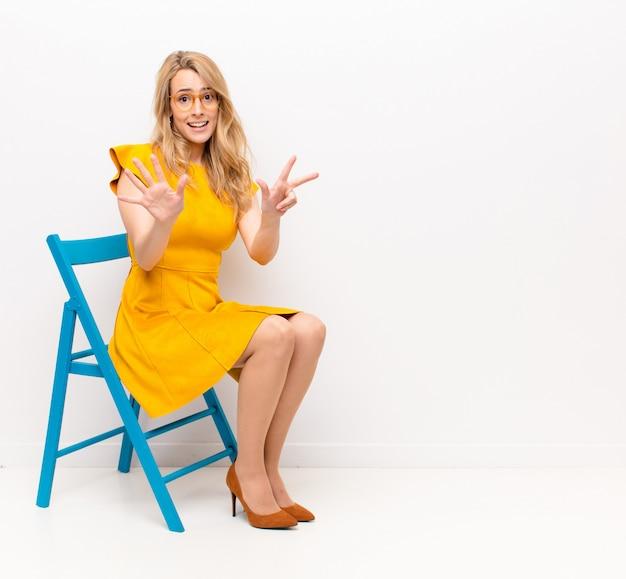 Junge hübsche blonde frau lächelt und sieht freundlich aus, zeigt nummer acht oder acht mit der hand nach vorne, zählt gegen flache farbwand herunter