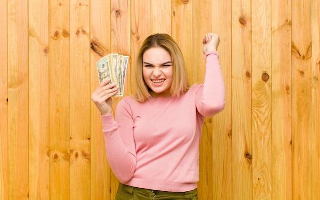 Junge hübsche blonde frau mit dollarbanknoten