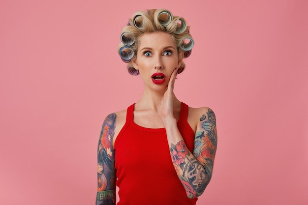Junge hübsche blonde frau mit offenen augen mit tätowierungen und festlichem make-up, die handfläche auf ihrer wange hält und erstaunt in die kamera schaut und sich auf bevorstehende party vorbereitet, isoliert über rosa hintergrund