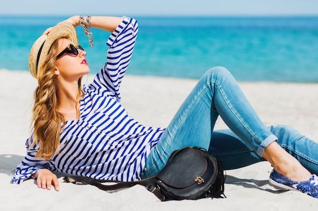 Junge hübsche blonde frische junge frau, die auf sand sitzt und davon träumt