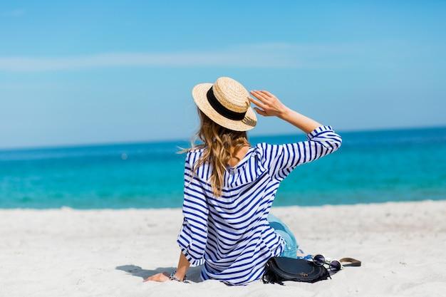 Junge hübsche blonde gebräunte junge frau, die am strand nahe dem meer zurück wartet und träumt