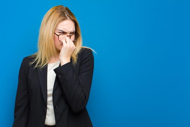 Junge hübsche blondine, die angewidert sich fühlen und nase halten, um zu vermeiden, einen faulen und unangenehmen gestank gegen flache wand zu riechen