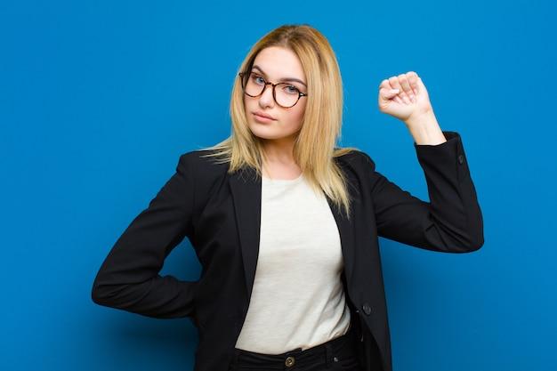 Junge hübsche blondine, die ernst, stark und rebellisch sich fühlen, faust oben anheben, für revolution protestieren oder kämpfen