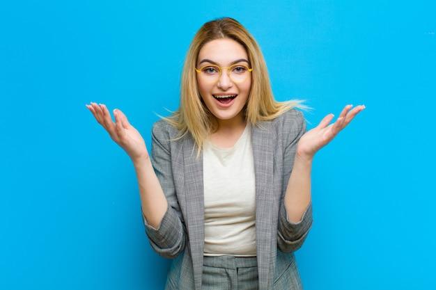 Junge hübsche blondine, die glücklich, aufgeregt, überrascht oder entsetzt sind und über etwas unglaubliches gegen wohnung lächeln und erstaunt sind