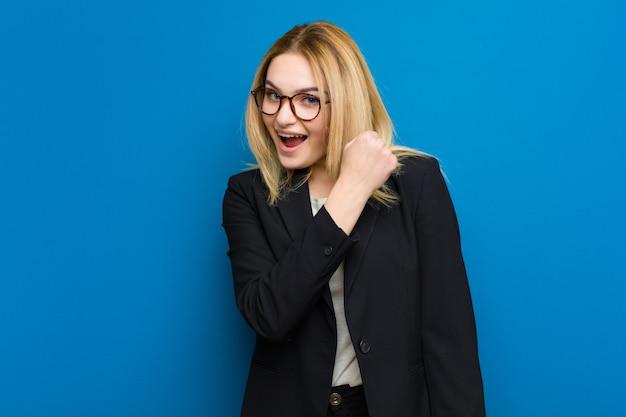 Junge hübsche blondine, die sich glücklich, positiv und erfolgreich fühlen, motiviert, wenn sie sich einer herausforderung stellen oder gute ergebnisse feiern