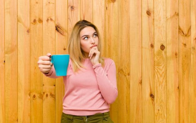 Junge hübsche blondine mit einer kaffeetasse gegen hölzerne wand