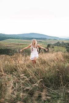 Junge hübsche boho-hippiefrau, die im rustikalen stil trägt, der im dorf ruht