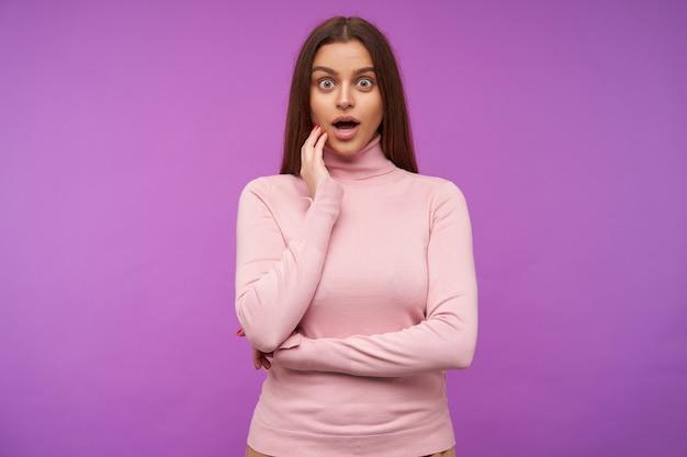 Junge hübsche braunhaarige frau mit offenen augen in rosa poloneck, die ihr gesicht mit erhobener hand berührt, während sie erstaunt nach vorne schaut und über lila wand posiert