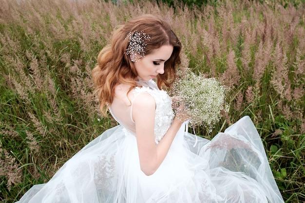 Junge hübsche braut im weißen hochzeitskleid im freien
