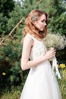 Junge hübsche braut mit geschlossenen augen im weißen hochzeitskleid halten blumenstrauß im freien