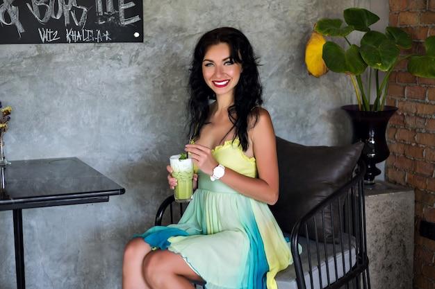 Junge hübsche brünette frau, die elegantes sommerkleid trägt, im café poring, leckeren cocktail trinkt und auf ihre freunde wartet.
