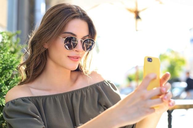 Junge hübsche brünette frau im freien in der sommerstadt machen ein selfie mit dem handy.