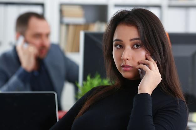 Junge hübsche brünette frau in der büroarbeit mit ihrem chef halten telefon in händen