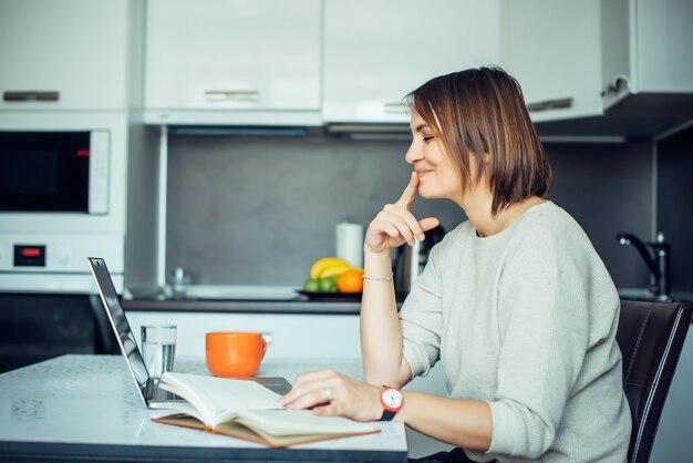 Junge hübsche brünette mit laptop an einem tisch in der küche sitzen. schriftstellerin arbeitet zu hause und trinkt kaffee. freiberuflich, remote-arbeit, kreativität.
