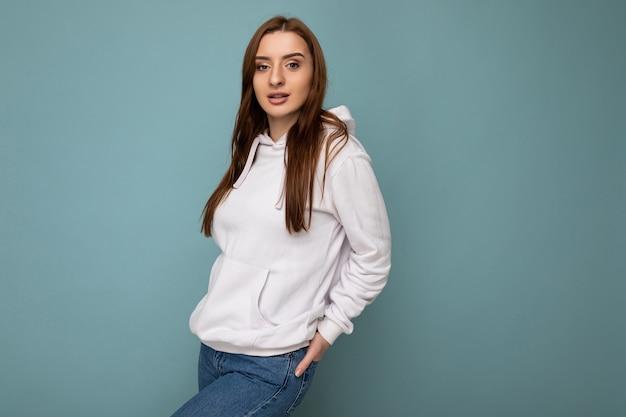 Junge hübsche brünette weibliche person mit aufrichtigen emotionen auf hintergrundwand mit kopie isoliert