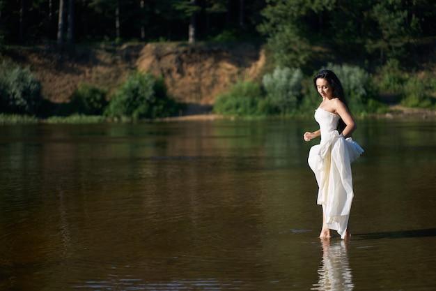 Junge hübsche brunettefrau im weißen hochzeitskleid barfuß gehend auf den fluss