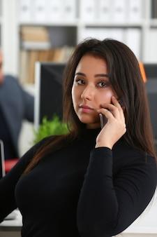 Junge hübsche brunettefrau in der büroarbeit mit ihrem chefgriff smartphone in den händen