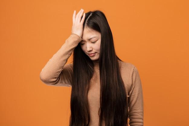 Junge hübsche chinesische frau, die etwas vergisst, stirn mit palme schlägt und augen schließt