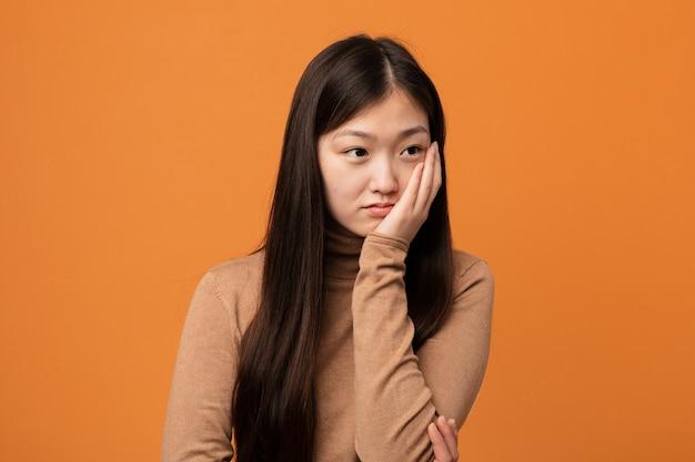 Junge hübsche chinesische frau, die gelangweilt, müde ist und einen entspannungstag benötigt.